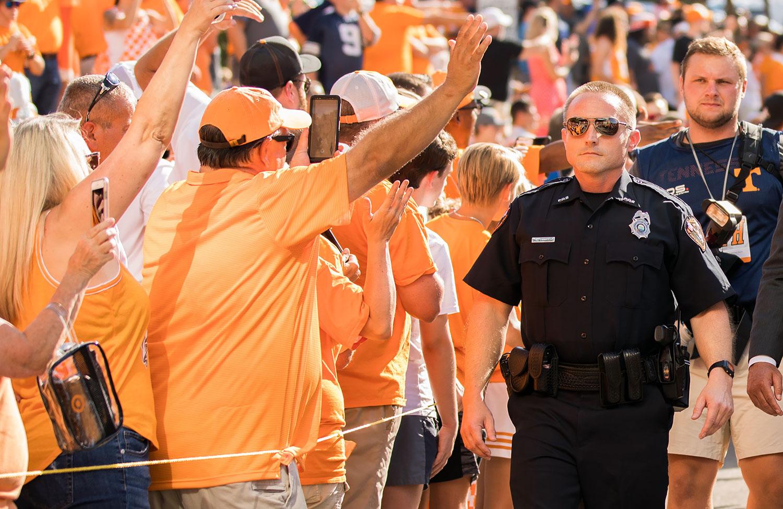 A uniformed UTPD officer walks past throngs of cheering football fans